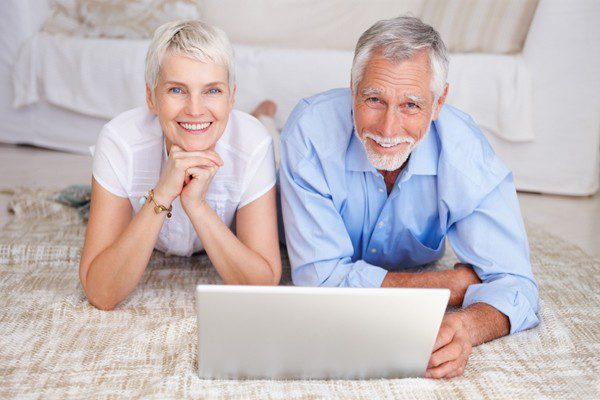 Happy senior couple lying down with a laptop, The Myndset Digital Marketing and Brand Strategy